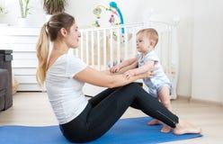 Giovane madre che allunga sulla stuoia di forma fisica con il suo neonato Fotografie Stock