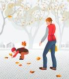 Giovane madre che cammina con il suo bambino che raccoglie le foglie cadute Immagini Stock