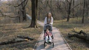 Giovane madre che cammina con una neonata in passeggiatore nel parco stock footage
