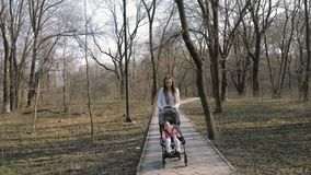 Giovane madre che cammina con una neonata in passeggiatore nel parco archivi video
