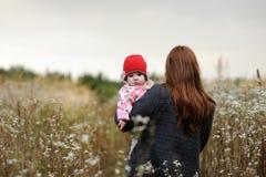 Giovane madre che cammina via tenendo il suo bambino. fotografia stock libera da diritti
