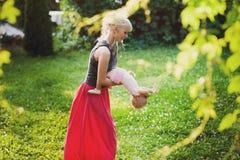 Giovane madre che gioca con la sua piccola figlia sulla natura Immagini Stock