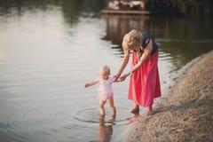 Giovane madre che gioca con la sua piccola figlia sulla natura Fotografia Stock Libera da Diritti