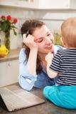 Giovane madre che lavora con il suo bambino Fotografie Stock