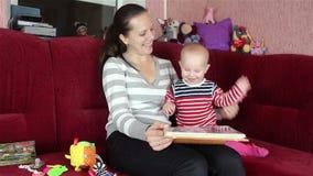 Giovane madre che legge un libro con il bambino video d archivio