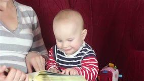 Giovane madre che legge un libro con il bambino archivi video