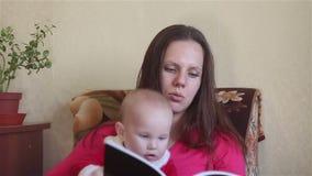 Giovane madre che legge un libro con il bambino stock footage