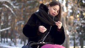 Giovane madre che mette sulle cuffie e che parla mentre camminando nel parco di inverno con il bambino in passeggiatore rosa Bell video d archivio