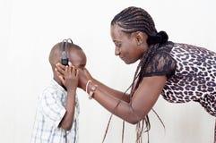 Giovane madre che porta un ascoltatore a suo figlio Immagini Stock Libere da Diritti