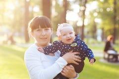 Giovane madre che porta una neonata e le passeggiate nel parco fotografie stock libere da diritti