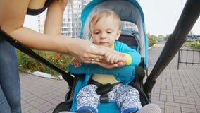 Giovane madre che pulisce le sue mani del neonato con il fazzoletto bagnato archivi video