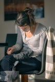 Giovane madre che ripara i vestiti fotografie stock libere da diritti