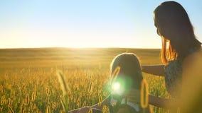 Giovane madre che si siede nel campo con la piccola figlia bionda e che indica al tramonto, donna felice con la ragazza all'apert archivi video