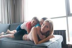 Giovane madre che spende tempo con i bambini sul pavimento Fotografie Stock