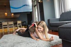 Giovane madre che spende tempo con i bambini sul pavimento Immagini Stock Libere da Diritti