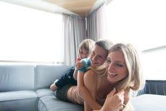 Giovane madre che spende tempo con i bambini sul pavimento Fotografia Stock Libera da Diritti