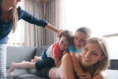Giovane madre che spende tempo con i bambini sul pavimento Immagine Stock Libera da Diritti