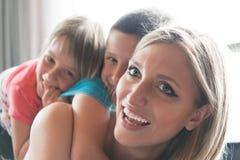 Giovane madre che spende tempo con i bambini sul pavimento Immagine Stock