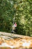 Giovane madre che spinge il suo bambino attraverso una foresta Fotografia Stock