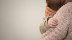 Giovane madre che stringe a sé infante adorabile in braccia, primo piano minuscolo della mano, cura del bambino video d archivio