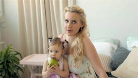 Giovane madre che tiene il suo bambino neonato Mamma della famiglia a casa e bambino, ragazza con gli occhi azzurri archivi video