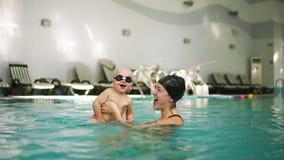 Giovane madre che tiene il suo ragazzino in vetri di protezione e che insegna a come nuotare nella piscina Respinta del bambino video d archivio