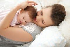Giovane madre che tiene piccolo bambino sveglio sul letto immagini stock libere da diritti