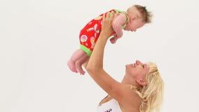 Giovane madre che tiene suo figlio in alto archivi video