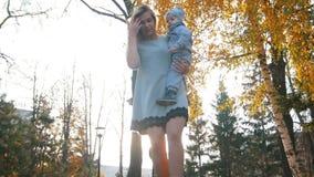 Giovane madre che va giù verso la macchina fotografica che tiene un bambino stock footage