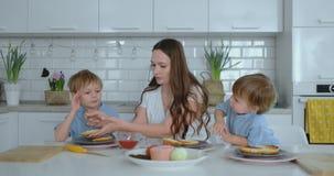 Giovane madre con due giovani figli nella cucina alla tavola che prepara hamburger per il pranzo video d archivio