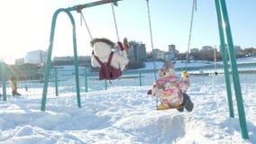 Giovane madre con il bambino che oscilla su all'aperto stabilito dell'oscillazione nel parco di inverno Neve che cade, precipitaz