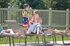 Giovane madre con il figlio alla piscina Immagine Stock
