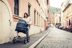 Giovane madre con il passeggiatore di bambino nella città Immagine Stock Libera da Diritti