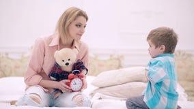 Giovane madre con il piccoli figlio sveglio e l'orsacchiotto che si siedono sul letto a casa La famiglia amichevole, una giovane  archivi video