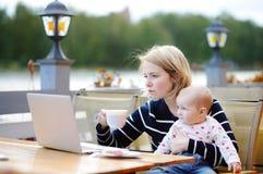 Giovane madre con il suo bambino che lavora o che studia sul computer portatile Immagine Stock