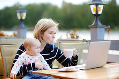 Giovane madre con il suo bambino che lavora o che studia sul computer portatile Fotografie Stock
