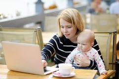 Giovane madre con il suo bambino che lavora o che studia sul suo computer portatile Fotografie Stock Libere da Diritti