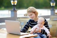 Giovane madre con il suo bambino che lavora o che studia sul suo computer portatile Fotografia Stock