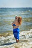 Giovane madre con il suo bambino che sta sulla spiaggia Fotografia Stock