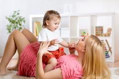 Giovane madre con il suo bambino divertendosi passatempo fotografie stock libere da diritti