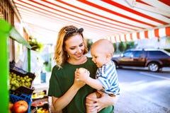Giovane madre con il suo neonato al mercato all'aperto Immagini Stock