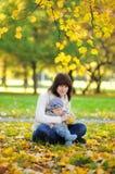 Giovane madre con il suo piccolo bambino nel parco di autunno Immagini Stock