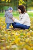 Giovane madre con il suo piccolo bambino nel parco di autunno Immagine Stock