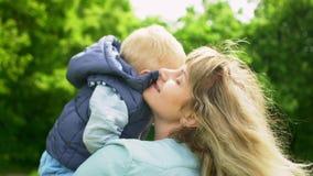 Giovane madre con il suo piccolo figlio che si rilassa e che gioca nel parco archivi video