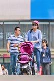 Giovane madre con l'automobile di bambino sul ponte pedonale, Pechino, Cina Immagine Stock