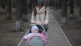 Giovane madre con la carrozzina che cammina in primavera parco Concetto 'nucleo familiare' e di amore stock footage