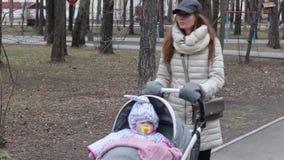 Giovane madre con la carrozzina che cammina in primavera parco Concetto 'nucleo familiare' e di amore archivi video