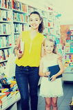 Giovane madre con la figlia nel negozio di libro Immagini Stock