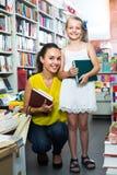 Giovane madre con la figlia nel negozio di libro Immagini Stock Libere da Diritti