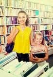 Giovane madre con la figlia nel negozio di libro Fotografie Stock Libere da Diritti